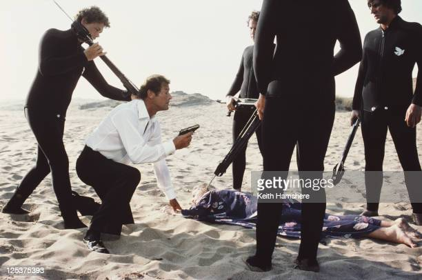 English actor Roger Moore kneels by the body of actress Cassandra Harris as Countess Lisl von Schraff in a scene from the James Bond film 'For Your...