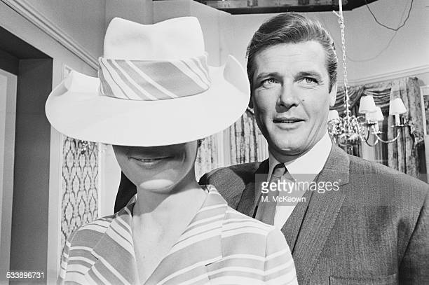 English actor Roger Moore on the set of the British TV series 'The Saint' with model Angela Fountain at Associated British Elstree Studios in...