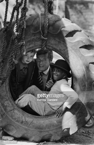 English actor Roger Moore playing with two children at an adventure playground, UK, 16th May 1973. He starred in the James Bond film 'Live and Let...