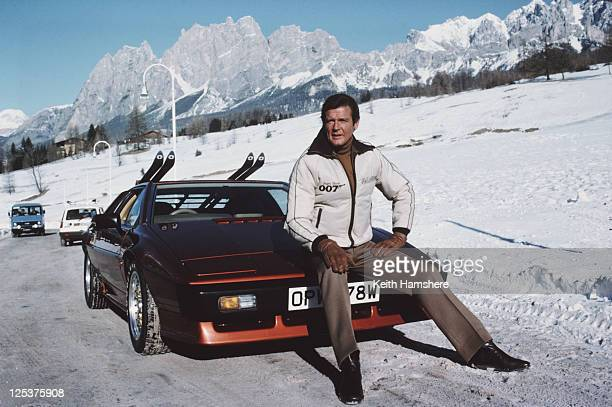 English actor Roger Moore poses as 007 with a Lotus Esprit Turbo on the set of the James Bond film 'For Your Eyes Only' February 1981