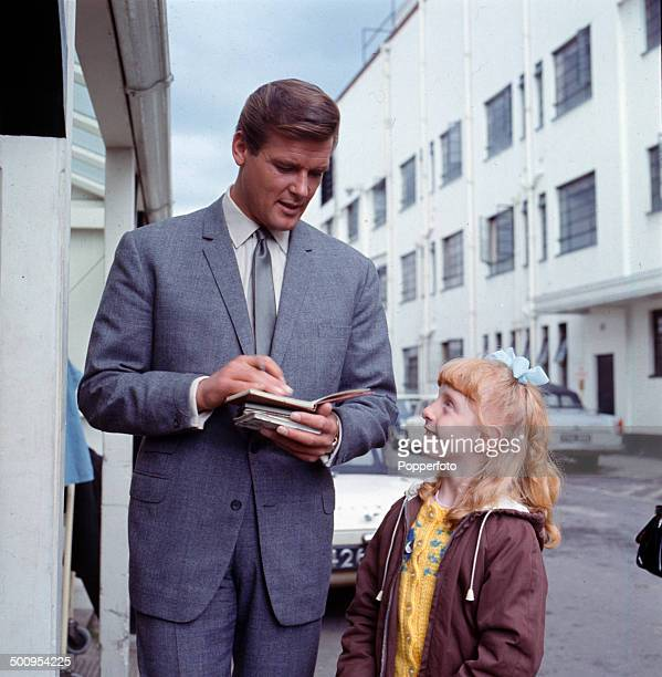English actor Roger Moore signs an autograph for a young female fan at Elstree Studios in Hertfordshire England during filming of the televsion...