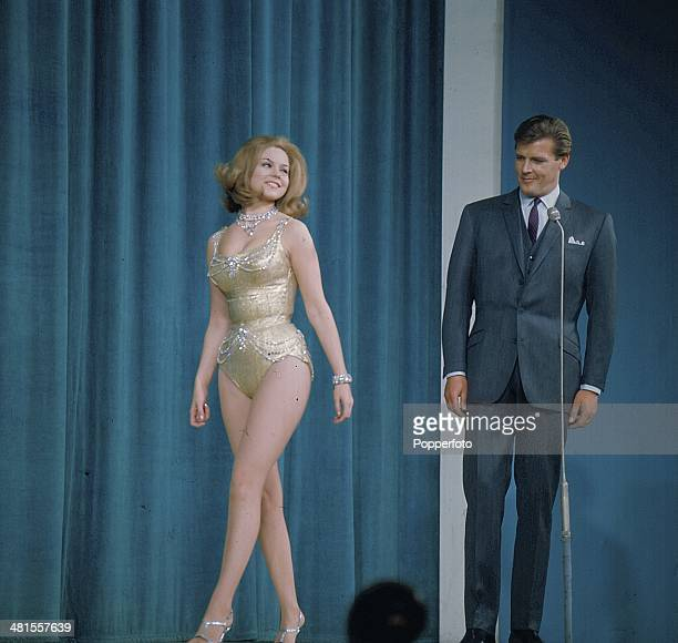 1968 English actor Roger Moore stands on stage with a female hostess on the set of the 'Hippodrome Show' on television in 1968