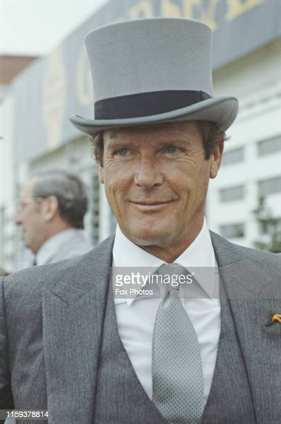 English actor Roger Moore wearing a top hat at the Epsom Derby, England, 5th June 1985.