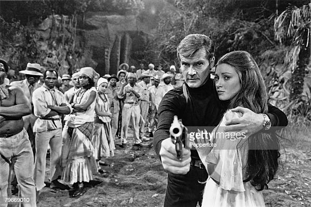 English actor Roger Moore who plays James Bond in the latest Bond film 'Live and Let Die' on the set with costar Jane Seymour 14th February 1973