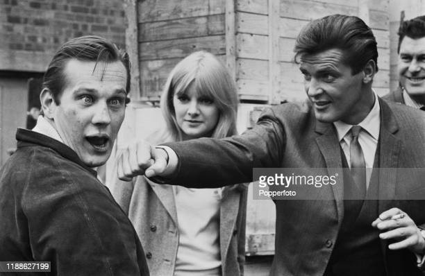 English actor Roger Moore who plays Simon Templar in the Incorporated Television Company television series 'The Saint' stands on right pretending to...