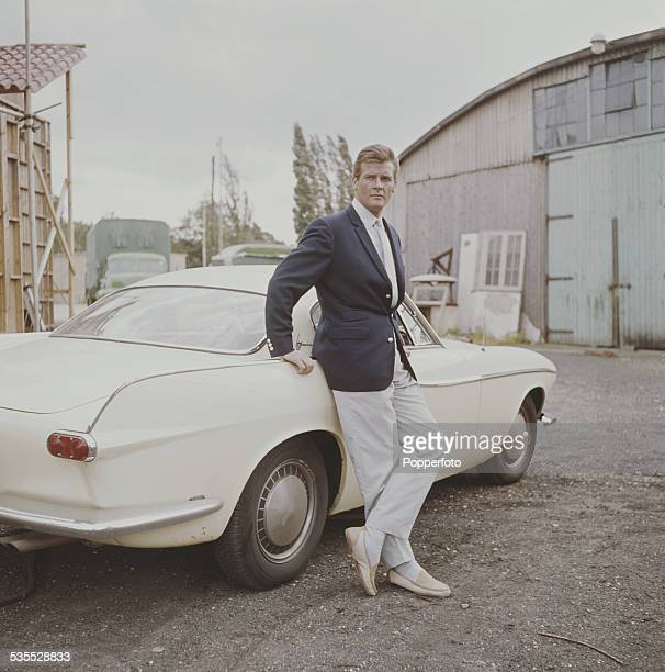 English actor Roger Moore who plays Simon Templar in the television series 'The Saint' pictured standing beside a Volvo P1800 car at Elstree Studios...