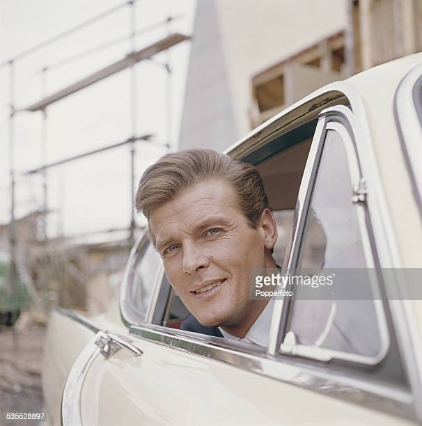 English actor Roger Moore who plays Simon Templar in the television series 'The Saint' pictured sitting in the driver's seatof a Volvo P1800 car at...