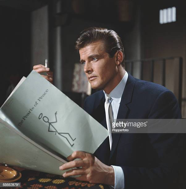 English actor Roger Moore who plays the character of Simon Templar in the television series 'The Saint' pictured holding a script for The Pearls Of...