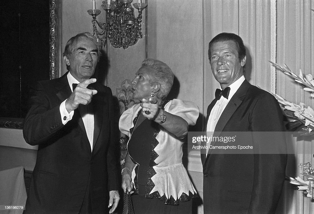 English actor Roger Moore with Gregory Peck and Maria Pia Fanfani at the Tribute To Ingrid Gala, Lido, Venice, 1983.