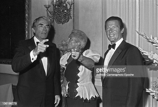 English actor Roger Moore with Gregory Peck and Maria Pia Fanfani at the Tribute To Ingrid Gala Lido Venice 1983