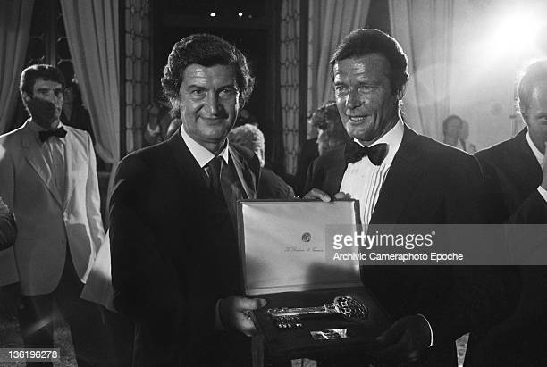 English actor Roger Moore with the Venice Mayor at the Tribute To Ingrid Gala Lido Venice 1983