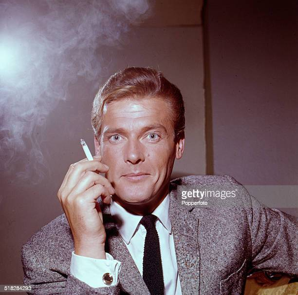 English actor Roger Moorewho stars in the television drama series 'The Saint' posed smoking a cigarette in 1965