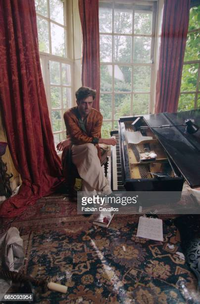 English actor Rupert Everett sitting on a tool poses in front of a piano with books cigarette butts papers an debris on the carpet around him on the...