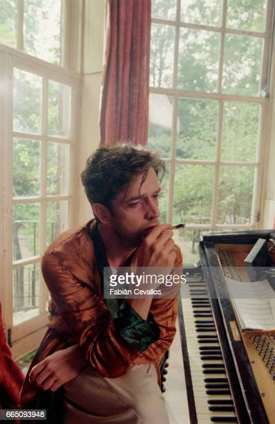English actor Rupert Everett wearing a brown bathrobe smokes in front of a piano with trees outside the window behind him on the set of the movie B...