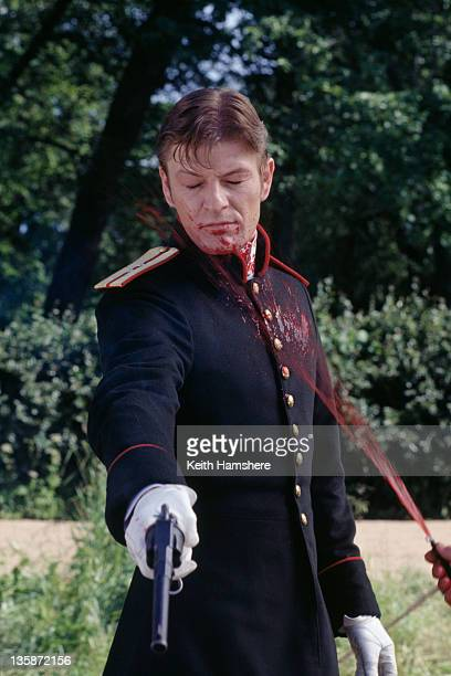 English actor Sean Bean as Vronsky in the film 'Leo Tolstoy's Anna Karenina' 1997 A technician squirts him with fake blood as he enacts the shooting...