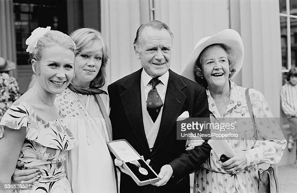 English actor Sir John Mills pictured holding his Knight Bachelor award with his wife actress Mary Hayley Bell and daughters Juliet Mills and Hayley...