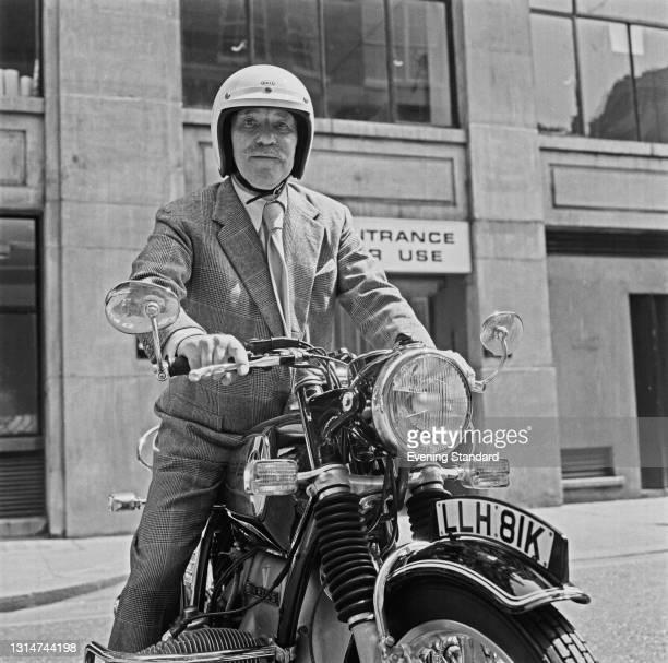 English actor Sir Ralph Richardson on his BMW R75 motorcycle, UK, 21st June 1974.
