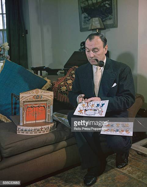 English actor Sir Ralph Richardson pictured making a model theatre out of cardboard at home on 19th November 1948