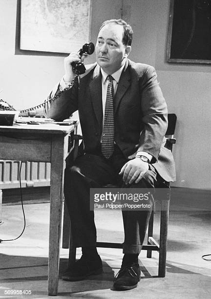 English actor Stratford Johns pictured in character as Inspector Barlow using a telephone in a scene from the television show 'ZCars' filmed at BBC...