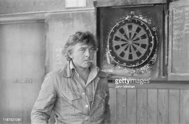 English actor, television director, and producer David Hemmings standing by a dartboard in a pub, UK, 22nd June 1976.