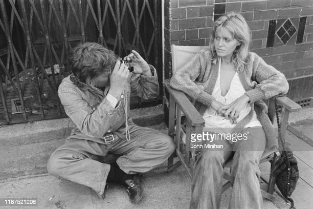 English actor television director and producer David Hemmings taking a picture of English actress Carol White on the set of gangster thriller movie...