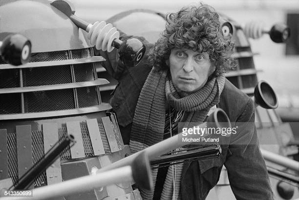 English actor Tom Baker as the Doctor from the BBC science fiction TV series 'Doctor Who' poses with the Doctor's arch enemies the Daleks at BBC TV...
