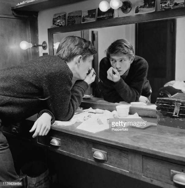 English actor Tom Courtenay pictured applying eye liner make up in a dressing room backstage at the Globe Theatre on Shaftesbury Avenue London in...