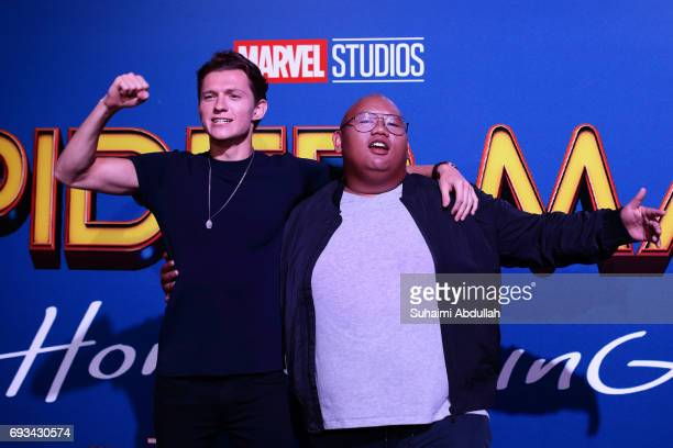 English actor Tom Holland and American actor Jacob Batalon react on stage during the SpiderMan Homecoming red carpet fan event at ArtScience Museum...