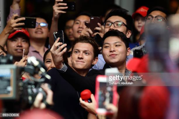 English actor Tom Holland takes selfie with fans at the SpiderMan Homecoming red carpet fan event at ArtScience Museum Marina Bay Sands on June 7...