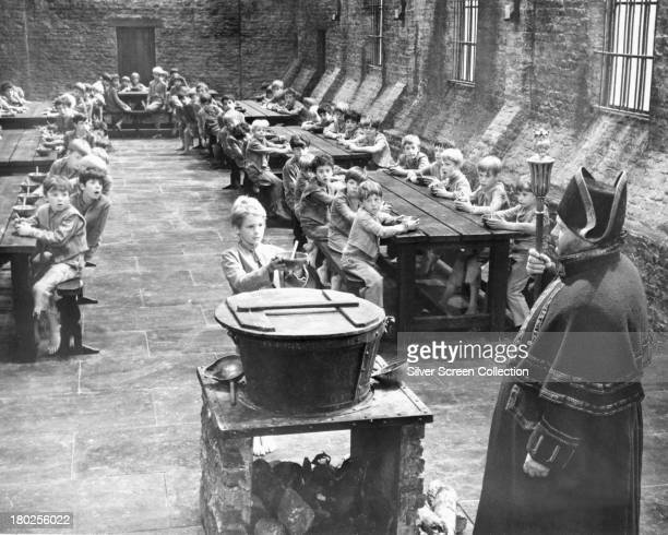 English actors Harry Secombe as Mr Bumble and Mark Lester as Oliver Twist in a workhouse scene from 'Oliver' directed by Carol Reed 1968