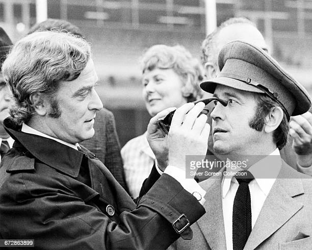 English actors Michael Caine as Jack Carter and Ian Hendry as Eric Paice in his chauffeur's uniform on the set of the film 'Get Carter' directed by...