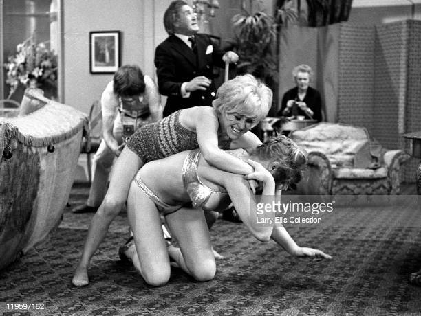 English actors Peter Butterworth and Robin Askwith watch feuding actresses Margaret Nolan and Barbara Windsor in the film 'Carry On Girls' 1973