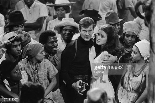 English actors Roger Moore and Jane Seymour surrounded by extras from the fictional Caribbean island of San Monique in the James Bond film 'Live And...