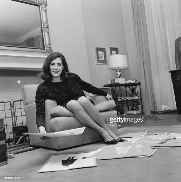 English actress and author Eleanor Bron looking at outfits designs in a living room UK 8th February 1965