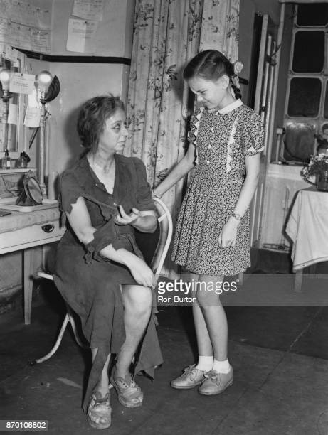 English actress and comedian Thora Hird earns a grimace from her daughter actress Janette Scott for her costume as Ada Lester in a stage production...