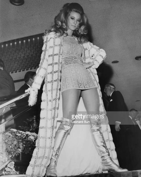 English actress and model Vicki Hodge wears a silver maxicoat over a crocheted minidress and silver boots to the premiere of the James Bond film 'On...
