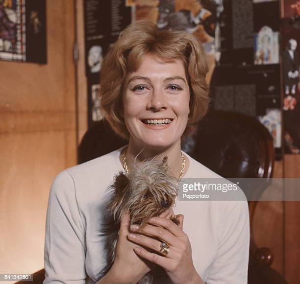 English actress and political activist Vanessa Redgrave pictured sitting in a high backed leather armchair holding a small dog at home in her flat in...