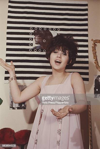 English actress and singer Adrienne Posta pictured singing in an apartment circa 1965