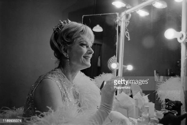 English actress and singer Anna Neagle seated in a dressing room backstage during a performance of the musical Charlie Girl at the Adelphi Theatre in...
