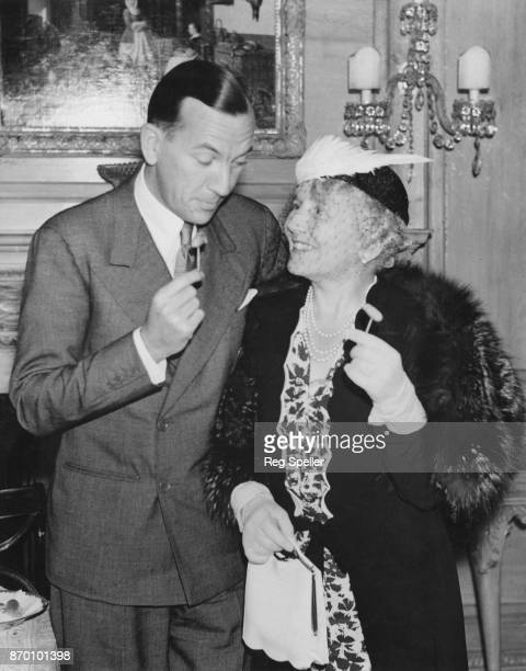 English actress and singer Ellaline Terriss , the wife of actor Sir Seymour Hicks, with Noel Coward at a cocktail party held by Lord and Lady Selsdon...