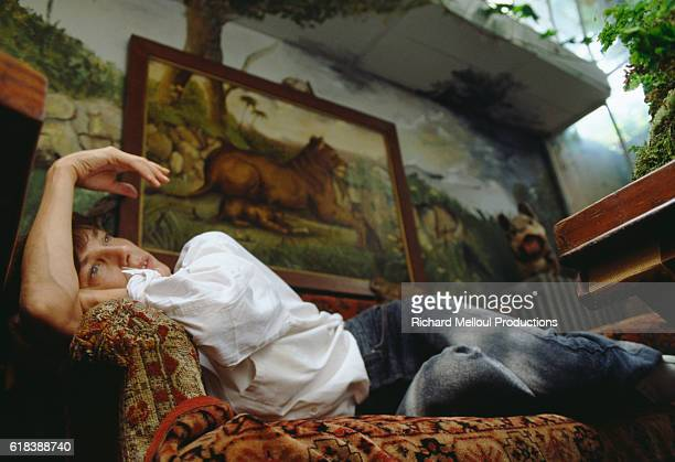 English actress and singer Jane Birkin reclines on a sofa in Paris