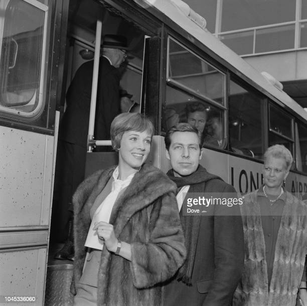 English actress and singer Julie Andrews pictured with her husband Tony Walton standing beside a transit bus at London airport on 9th September 1963....