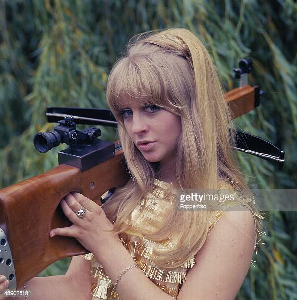 English actress and television host Carol Dilworth holds the crossbow featured in the television quiz show 'The Golden Shot' in 1967
