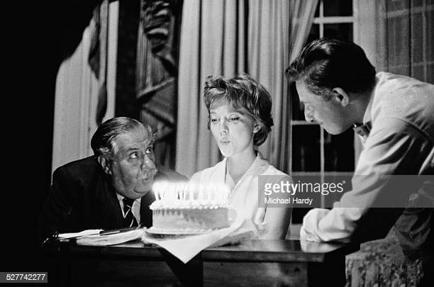 English actress Anna Massey blowing out candles on her 21st birthday cake as British theatrical manager Henry Sherek looks on, August 1958.