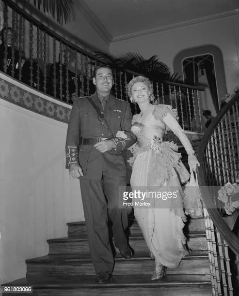 English actress Anna Neagle and actor Errol Flynn enter a reproduction of Romano's Restaurant on the Strand at the ABC studios in Elstree UK during...