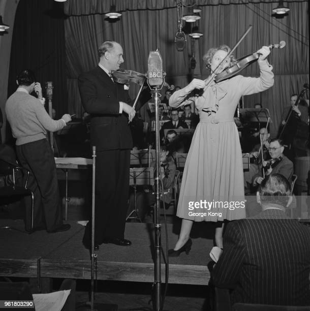 English actress Anna Neagle guest stars on a new series of the BBC comedy radio show 'Hi Gang' playing a violin duet with Vic Oliver February 1949