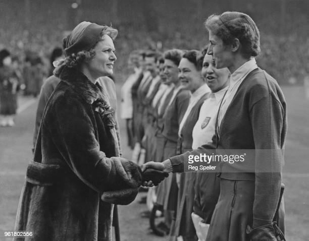 English actress Anna Neagle shakes hands with Mary Russell Vick of the England team during a women's international hockey match against Scotland at...