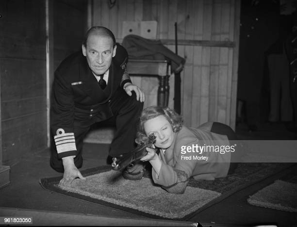 English actress Anna Neagle takes a shooting lesson from Admiral Sir Edward Evans during the institution of the London Region Rifle Association in...