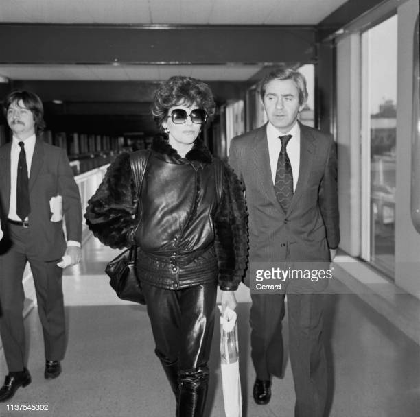 English actress author and columnist Joan Collins and Swedish singer Peter Holm at Heathrow Airport London UK 22nd November 1983