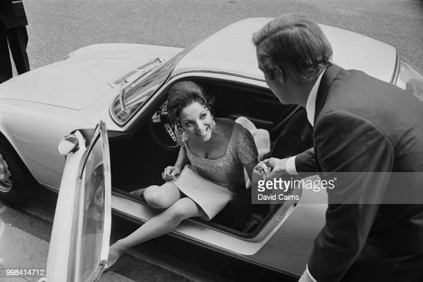 English actress author and columnist Joan Collins stepping out of a car with the help of American actor George Peppard during filming of 'The...